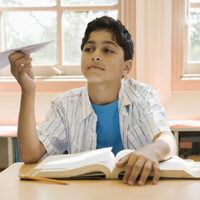 Boy in school at a desk with a paper airplane