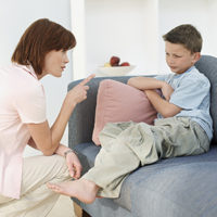 Mother pointing finger at boy age 8 or 9 in living room
