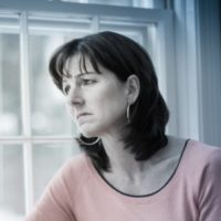 Estranged mom looking out window thinking of her child