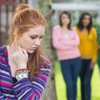 2 mean girls glaring a girl classmate