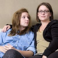 Mom sitting on couch with her teen daughter