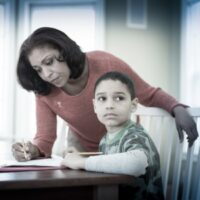 Mother doing homework for her child as child looks away