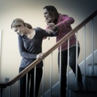 Mom and teen daughter fighting on stairs