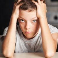 adolescent boy with hands on his head looking frustrated
