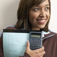 Teen girl holding notebook and calculator