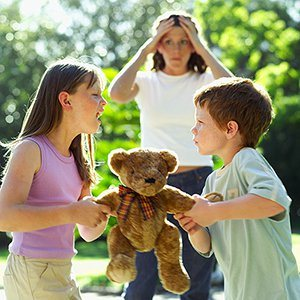 Brother and sister fighting over teddy bear with frustrated mom watching