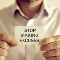 "Man holding note card that says ""STOP MAKING EXCUSES"""